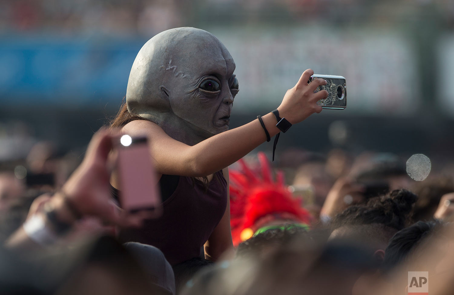 A woman wearing an extraterrestrial mask takes photos during the Vive Latino music festival in Mexico City, March 18, 2018. The two-day rock festival is one of the most important and longest running of Mexico. (AP Photo/Christian Palma)