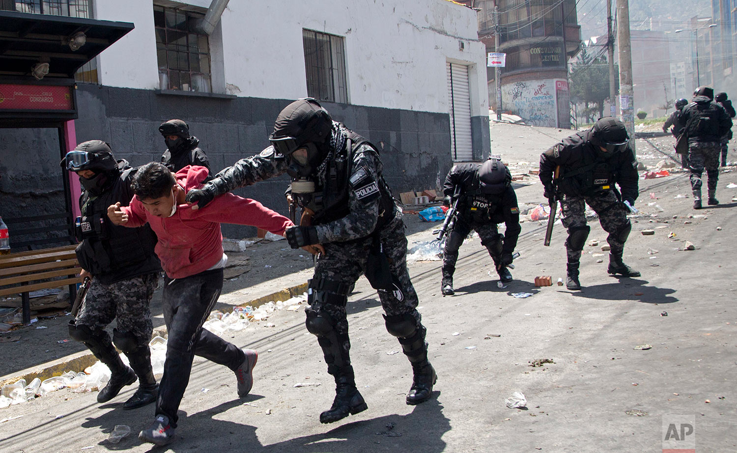 Police detain an anti-government coca farmer outside the coca market in La Paz, Bolivia, March 22, 2018. Anti-government coca farmers were again dispersed by police as they continued to try to take over the coca market by force, after losing access to it last week when pro-government coca growers, forced them out. (AP Photo/Juan Karita)