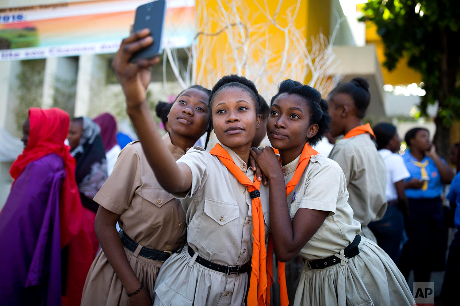 Girl scouts pose for a group photo at the third station of the Way of the Cross reenactment marking Good Friday, in Port-au-Prince, Haiti, March 30, 2018. Thousands of Haitians are commemorating the crucifixion of Jesus Christ by reenacting the Way of the Cross, visiting the 14 stations, each marking an event that befell Jesus Christ on his final journey. (AP Photo/Dieu Nalio Chery)