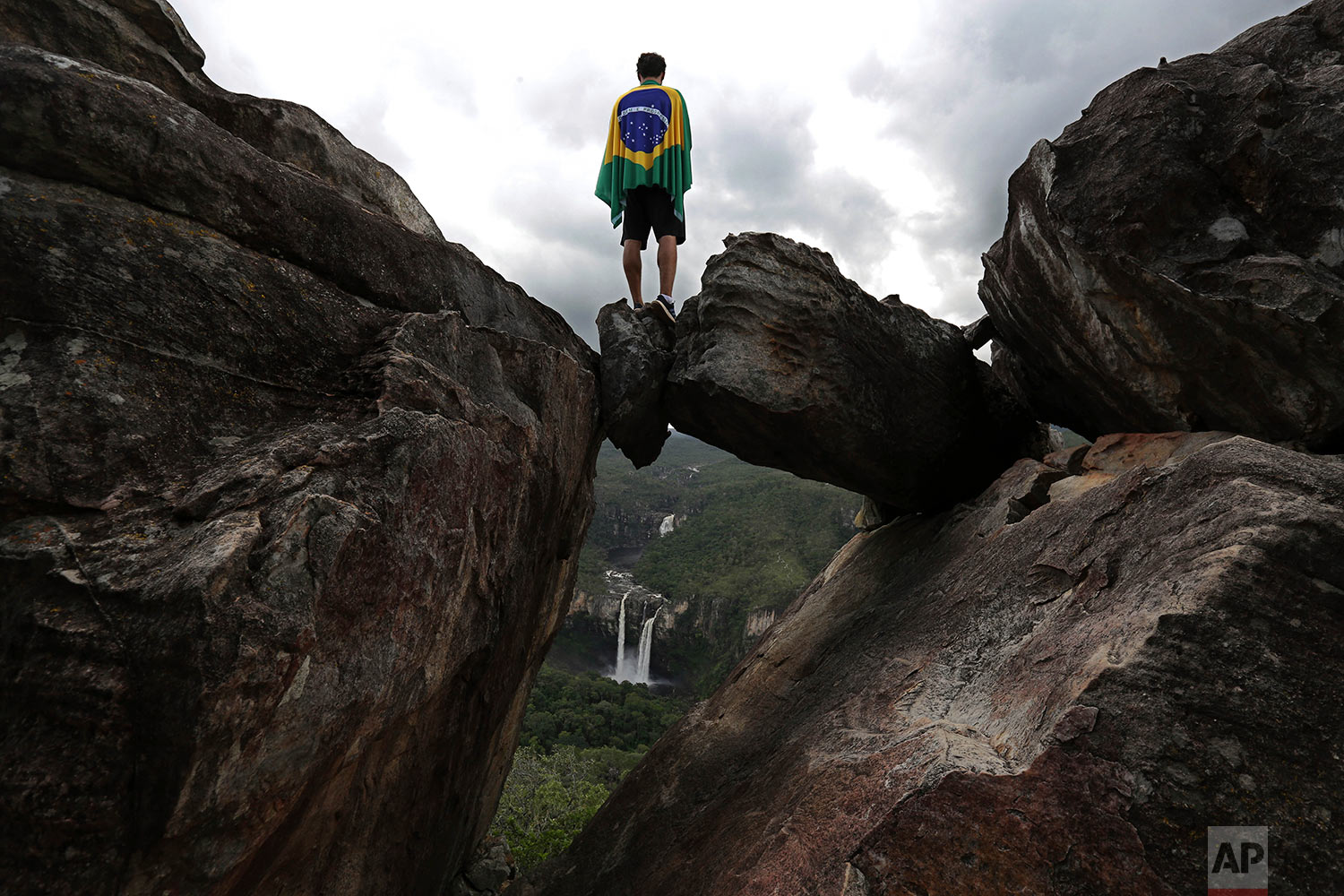 A park visitor wrapped in a Brazilian flag stands above a naturally forming window known as The Leap from Garimpo and looks out at the Salto do Rio Preto waterfall in Chapada dos Veadeiros National Park in Alto Paraiso, Goias state, Brazil, March 17, 2018. The nature reserve is recognized as one of country's main water cradles, and responsible for the formation of the Amazon basin, with springs that form the Tocantins River. Brazil will host the 8th World Water Forum starting Monday,  March 19. (AP Photo/Eraldo Peres)