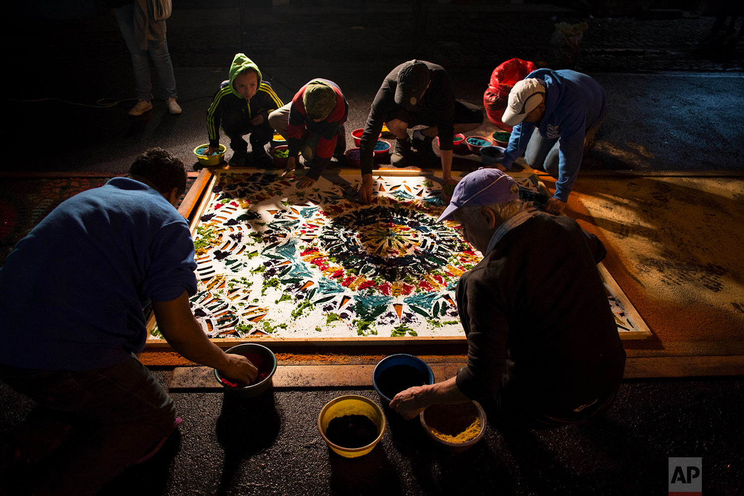 People retouch a carpet created from sawdust after a light rain, prior to the start of a Good Friday procession in Antigua, Guatemala, March 30, 2018. Many work overnight on these elaborate masterpieces that will disappear in a couple of minutes under the feet of dozens of penitents carrying in procession a 3-ton religious float. (AP Photo/Moises Castillo)