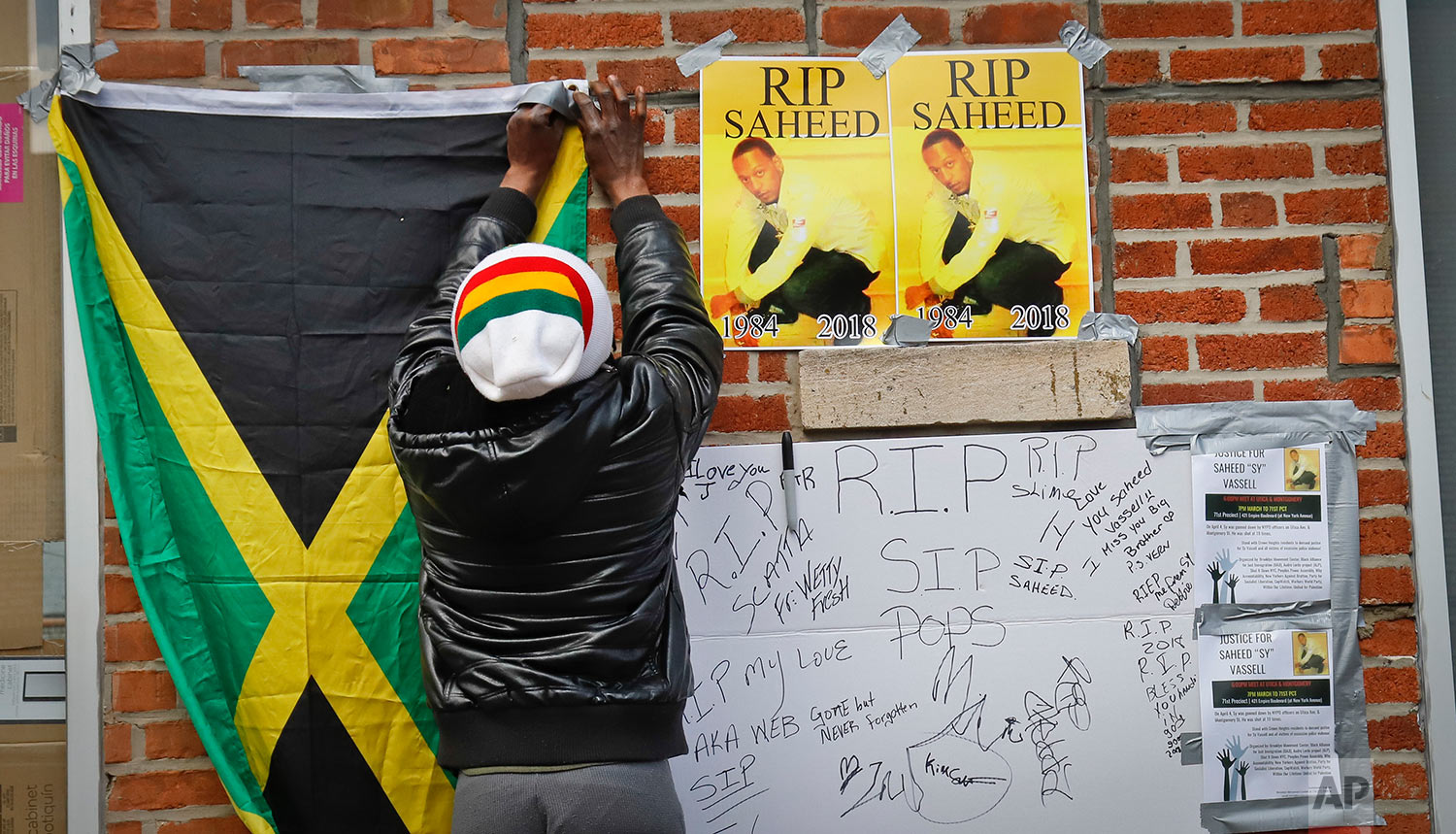 Jamaica's national flag is pinned at the site of a makeshift community memorial for Saheed Vassell, Thursday April 5, 2018, in New York. (AP Photo/Bebeto Matthews)