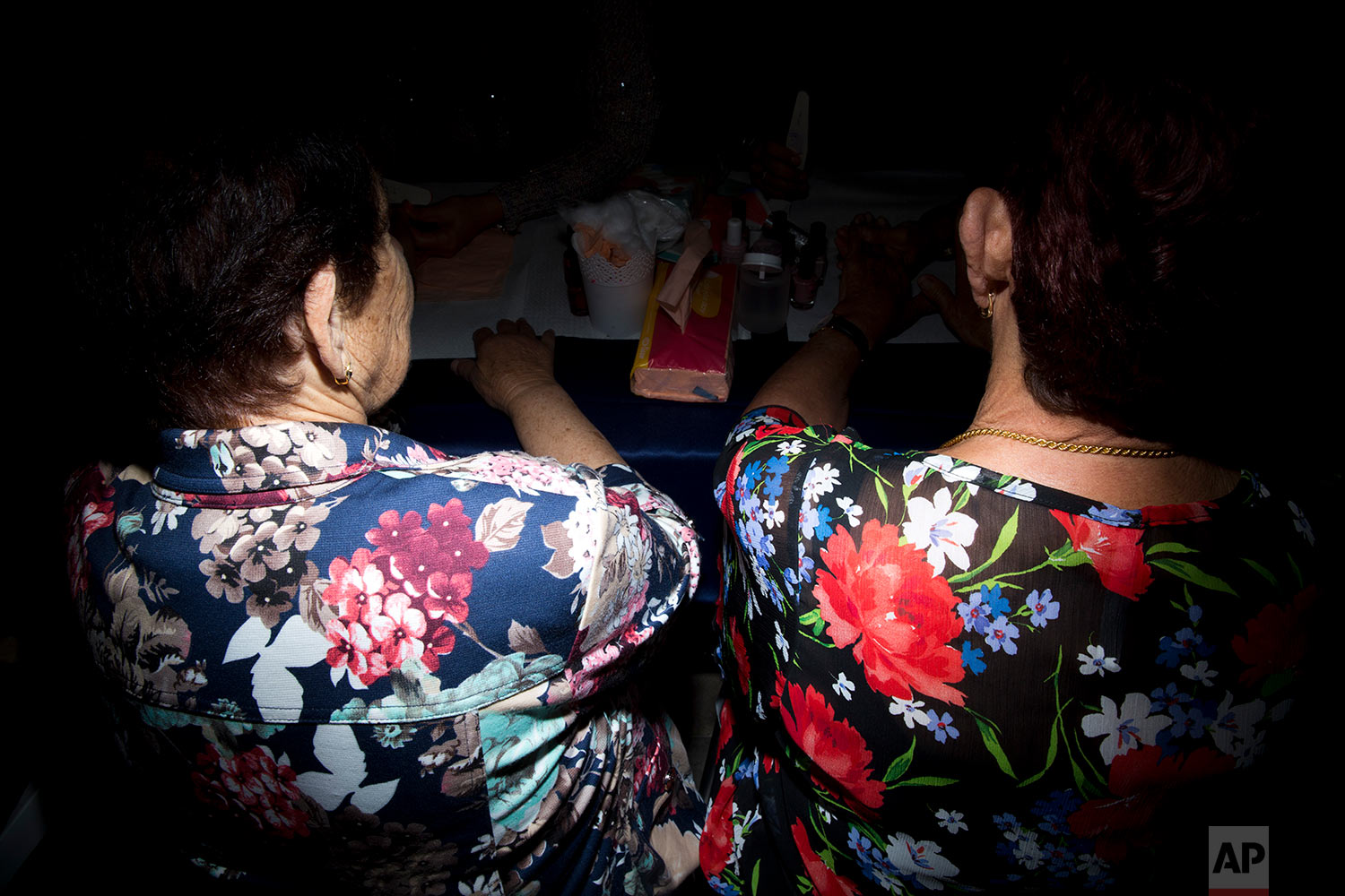 Two holocaust survivors has fingernail polish applied during a Beauty Heroines event in Ramat Gan, Israel, Monday, April 9, 2018.  (AP Photo/Oded Balilty)
