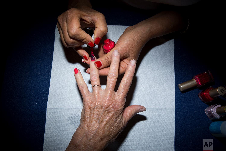 Holocaust survivor Hannah Beker, 79, has fingernail polish applied during a Beauty Heroines event in Ramat Gan, Israel, Monday, April 9, 2018.  (AP Photo/Oded Balilty)