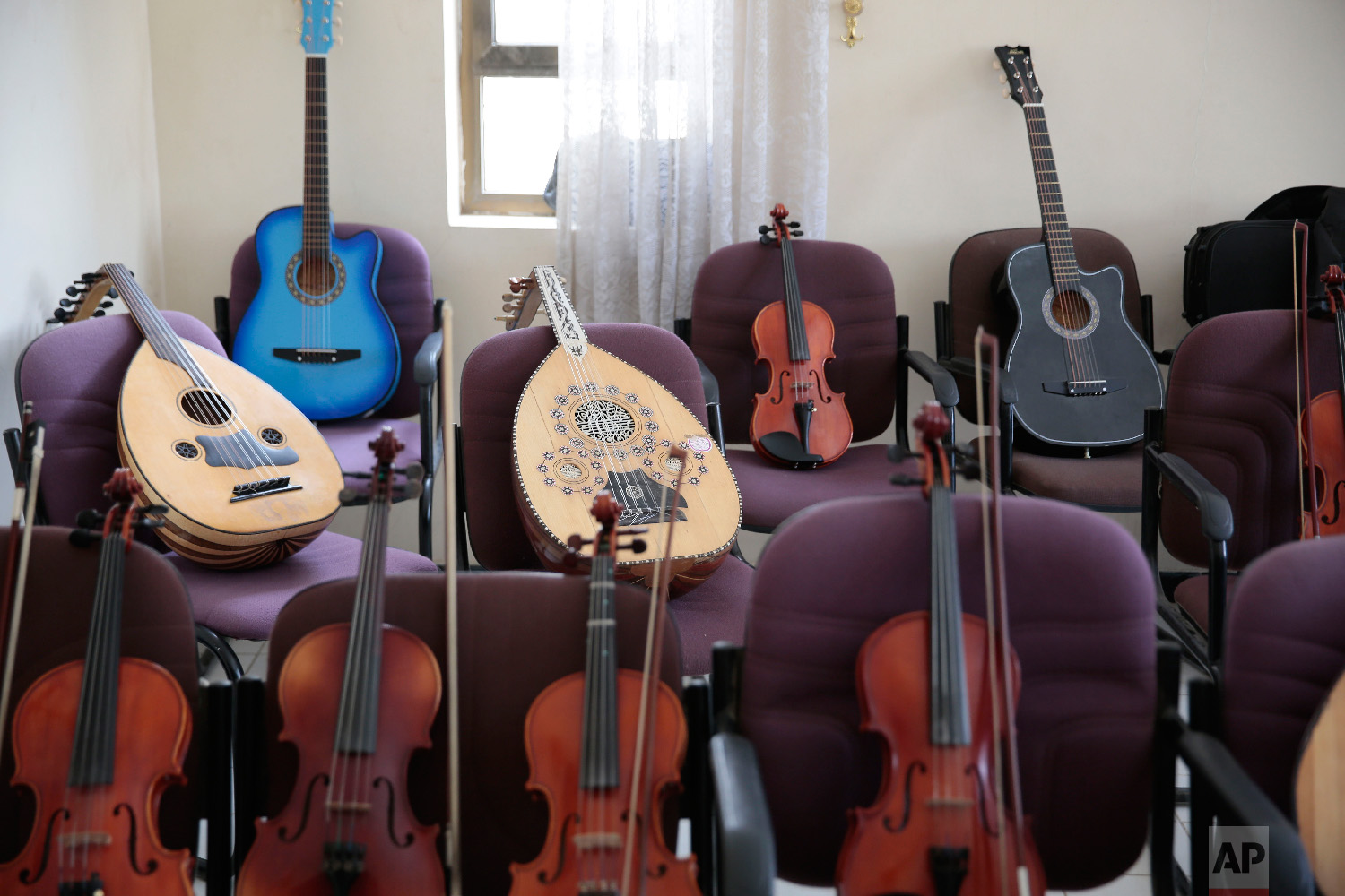 Musical instruments sit on chairs during a break of a music class at the Cultural Centre in Sanaa, Yemen on Monday, April 9, 2018.(AP Photo/Hani Mohammed)