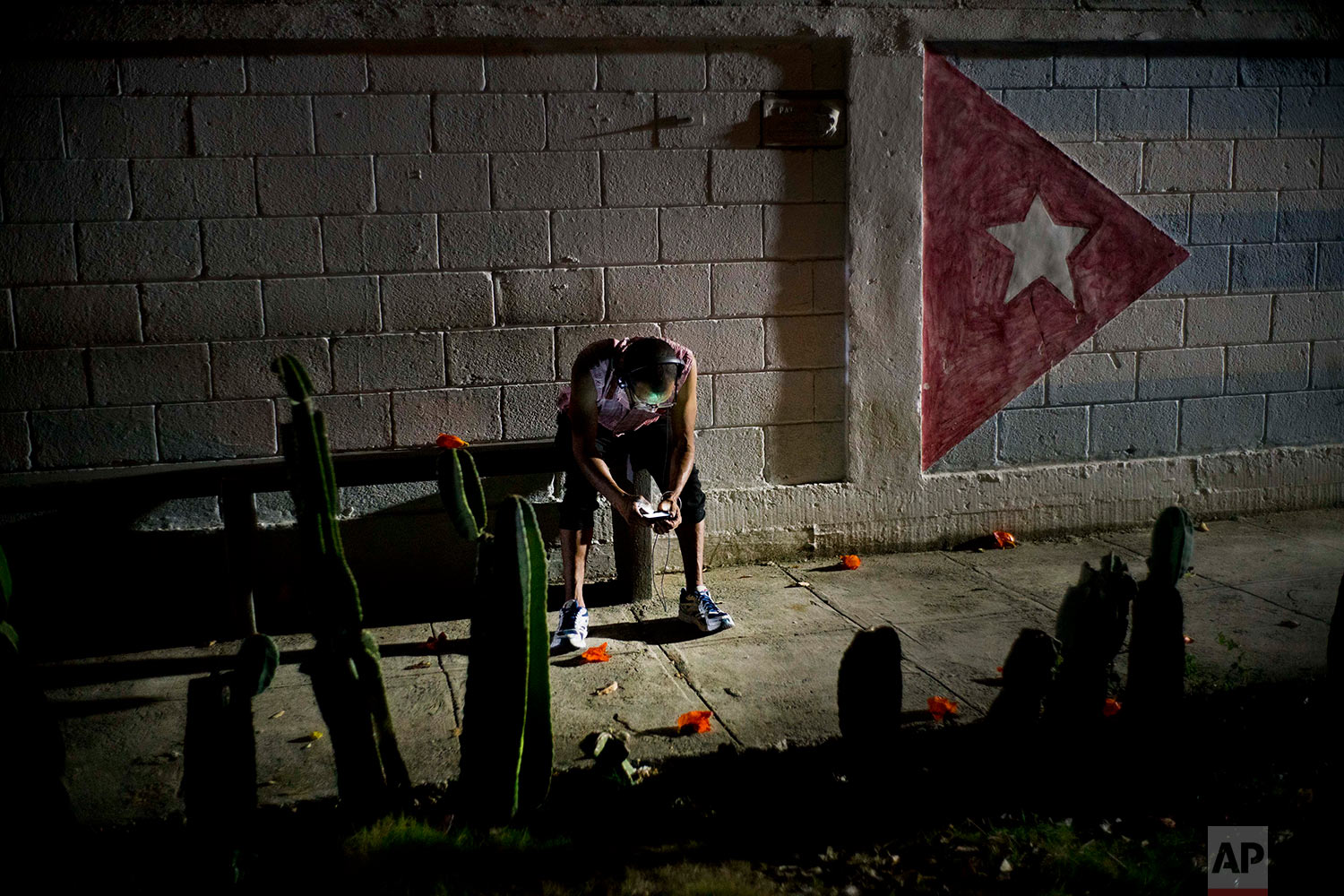 """In this April 14, 2018 photo, Lazaro Rodriguez, 42, connects his cell phone at a public internet hot spot at night in Havana, Cuba. Lazaro, who studied baking and is currently working in maintenance, said he's seen very positive changes in the economy in recent years, and would like to see development continue. """"The generation that comes after me will have much more. I lived 'the special period' in the 90s, and the country is still blocked,"""" referring to the U.S. embargo. (AP Photo/Ramon Espinosa)"""