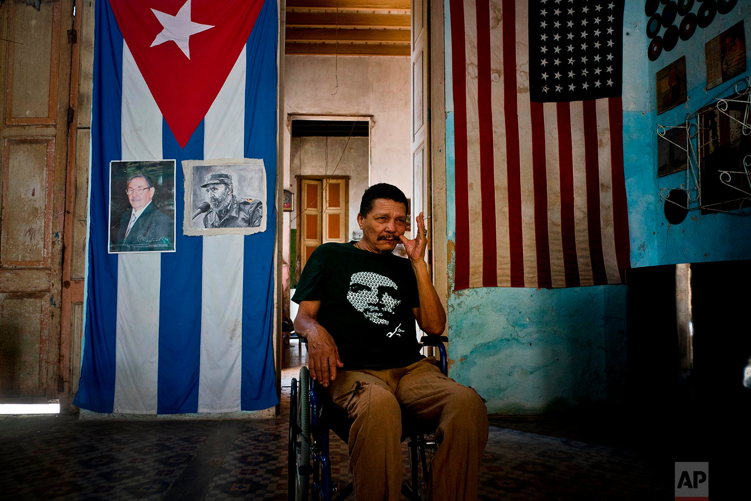 """In this April 12, 2018 photo, Armando Ricart Batista, a teacher by training, a former boxer and actor, poses next to Cuban and U.S. flags at his home, with the Cuban one carrying photos of Fidel and Raul Castro, in Havana, Cuba. Ricart, 65, said he's not affiliated with the Communist Party but hopes a new generation of leaders will follow the ideals of the Castros. He said he hangs the U.S. flag because relations with the U.S. improved under then-President Barack Obama, and the majority of American people are in favor of relations with Cuba. """"The American people are good,"""" he said. (AP Photo/Ramon Espinosa)"""