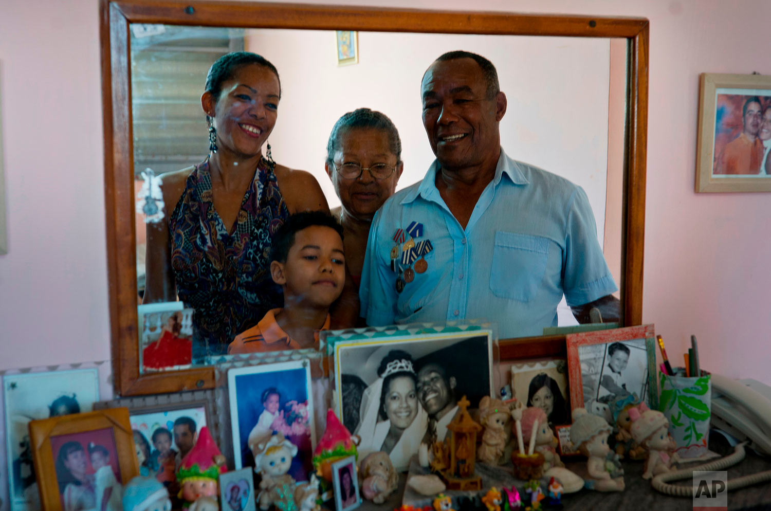 """In this April 14, 2018 photo, Amable Lopez, right, a Angola war veteran, poses with his family in Havana, Cuba. Lopez, a 69-year-old retiree, quit his university studies to join the team that built the famed, Soviet-style Alamar buildings. The former carpenter, firefighter and oil refinery worker said that compared to his generation's time, there is more development in Cuba and youths have everything they need to improve their lives. """"They need to improve the economy, raise salaries, lower prices. There are things that can be improved. Let's see what happens,"""" Lopez said. (AP Photo/Ramon Espinosa)"""