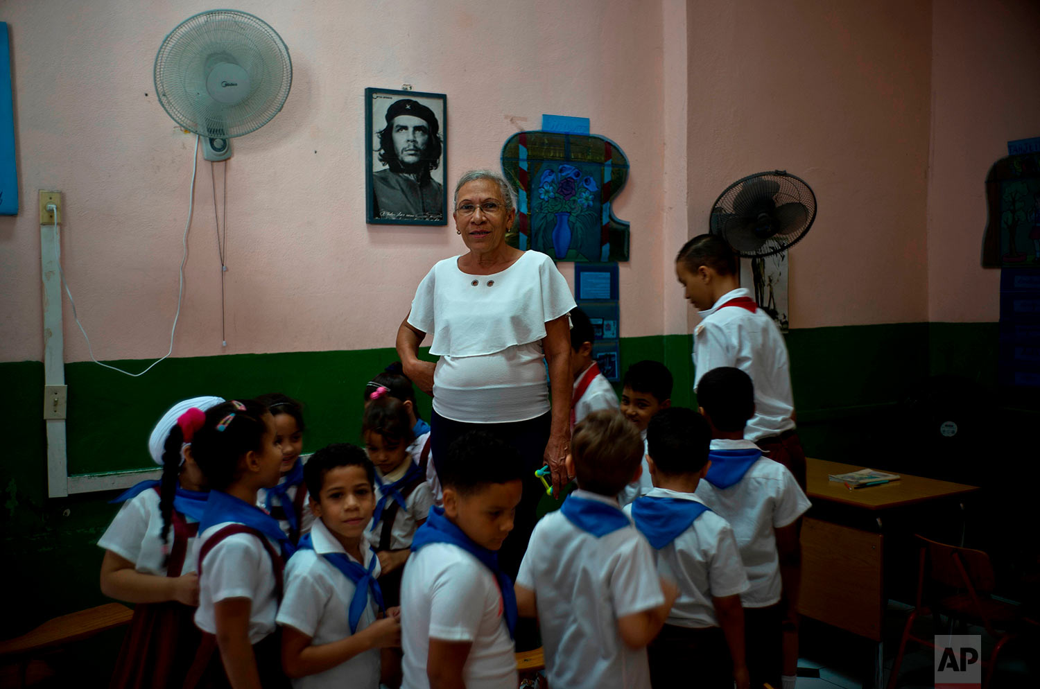 """In this April 13, 2018 photo, teacher Luisa Pacheco, 65, poses with her students in Havana, Cuba. Pacheco, who began teaching at the age of 14 in the Sierra Maestra's rural schools, said she likes education because she wants to train new generations for a good future and achieve what she did. When asked about Raul Castro's successor, she said """"I hope the new president will do what our commander Fidel Castro did,"""" adding that she wants the U.S. to remove its embargo against Cuba to help improve the economy. (AP Photo/Ramon Espinosa)"""