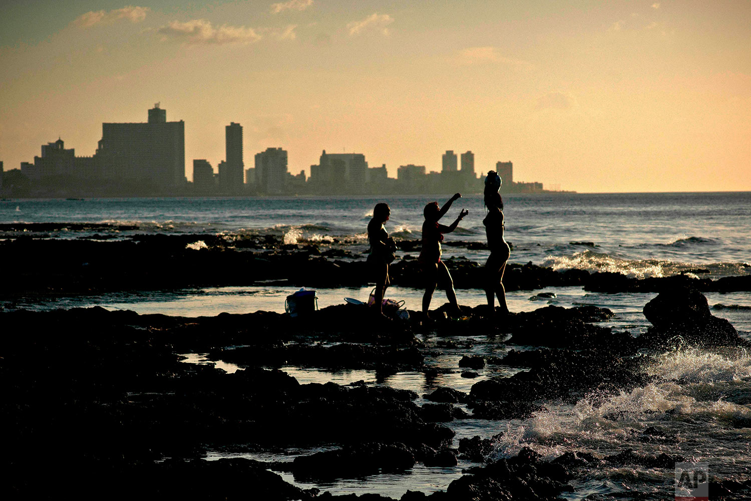 """In this April 14, 2018 photo, Santera Mailyn Lopez, center, performs a ritual with Mili Garcia Perez, right, and Zulay De Las Mercedes, on Chivo beach in Havana, Cuba. Mili and Zulay, who work at a restaurant, came to evoke the presence of """"Olokun,"""" a saint who according to Santeria lives in the sea and brings one health, prosperity and stability. (AP Photo/Ramon Espinosa)"""