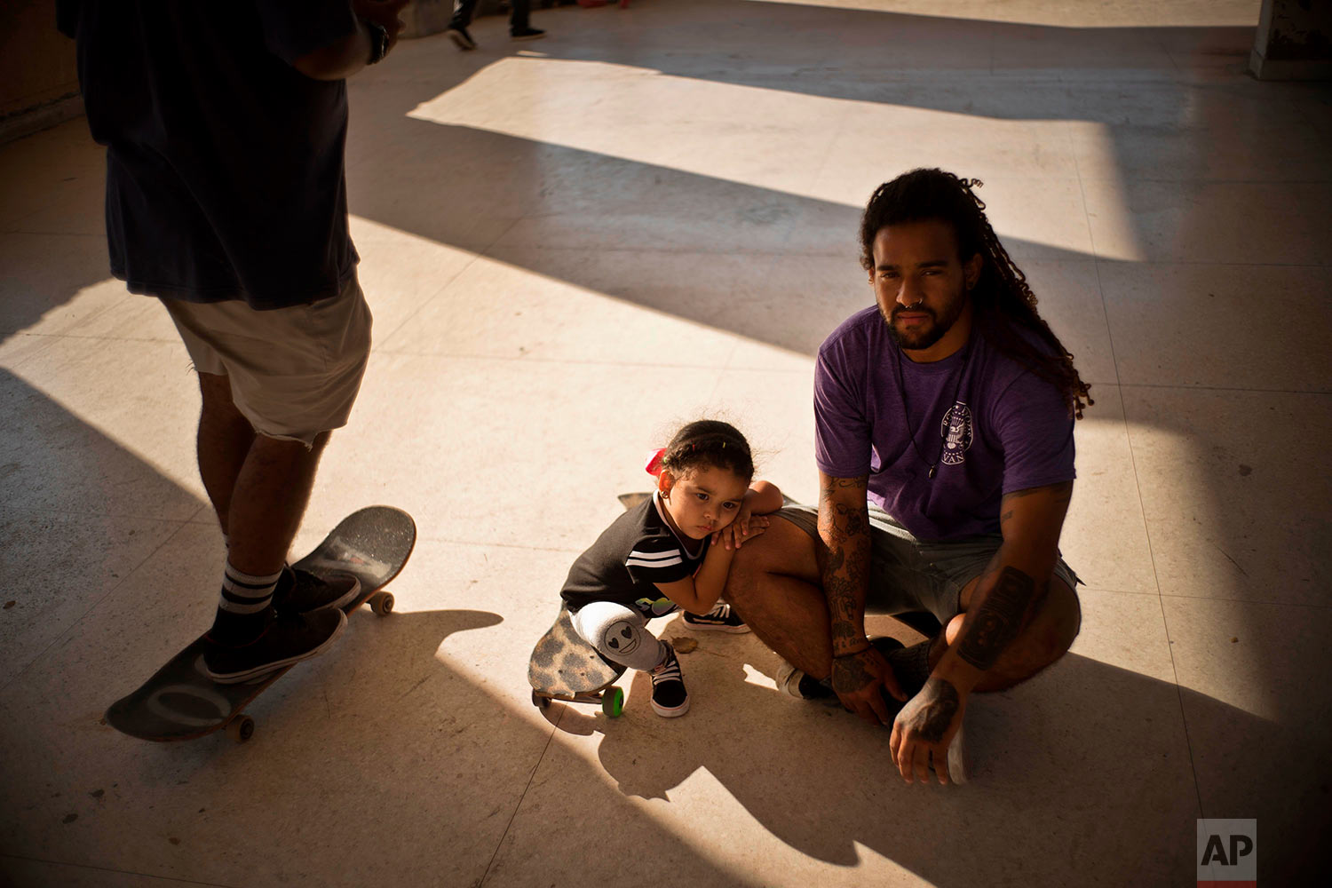 """In this April 12, 2018 photo, Yojany Perez, 28, poses for a photo with his 2-year-old daughter Coraline Perez Padilla, at a skateboarding park in Havana, Cuba. Perez, who has an economy degree but works in maintenance, said with the arrival of a new Cuban president on April 19, people are expecting an improvement in the economy, for prices to decline or salaries rise. """"Our current economy does not give for many luxuries,"""" Perez said. (AP Photo/Ramon Espinosa)"""