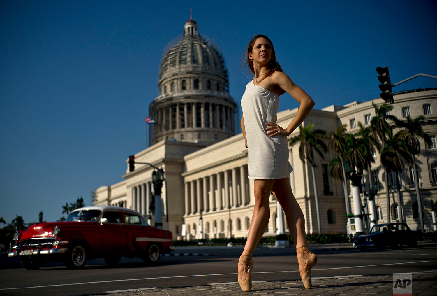In this April 14, 2018 photo, National Ballet of Cuba dancer Daniela Gomez Perez stands on point as she poses outside the Capitol in Havana, Cuba. Gomez, who says Cubans love dancing, trusts the next generation of leaders will continue such traditions and that art will continue to be the engine of Cuban society. Gomez said she is proud to represent Cuba during a dance trip in May to Washington, Tampa and Chicago, and that the Cuban state has always supported dance. (AP Photo/Ramon Espinosa)