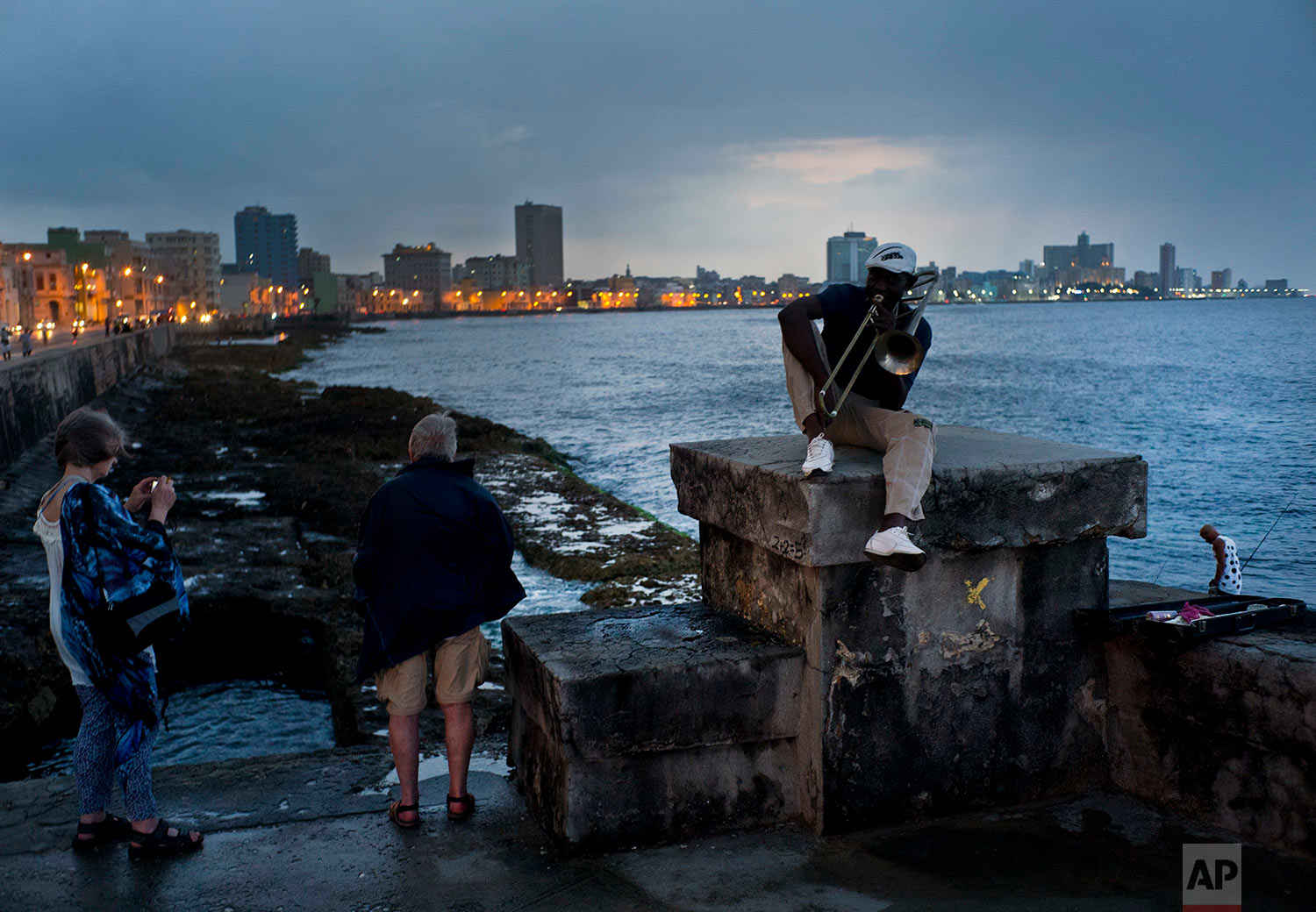 """In this April 13, 2018 photo, musician Lazaro Martinez poses with his trombone on the Malecon sea wall in Havana, Cuba. Since 1991, Martinez has regularly played his music at the Malecon. """"My politics are music,"""" said the 52-year-old. (AP Photo/Ramon Espinosa)"""