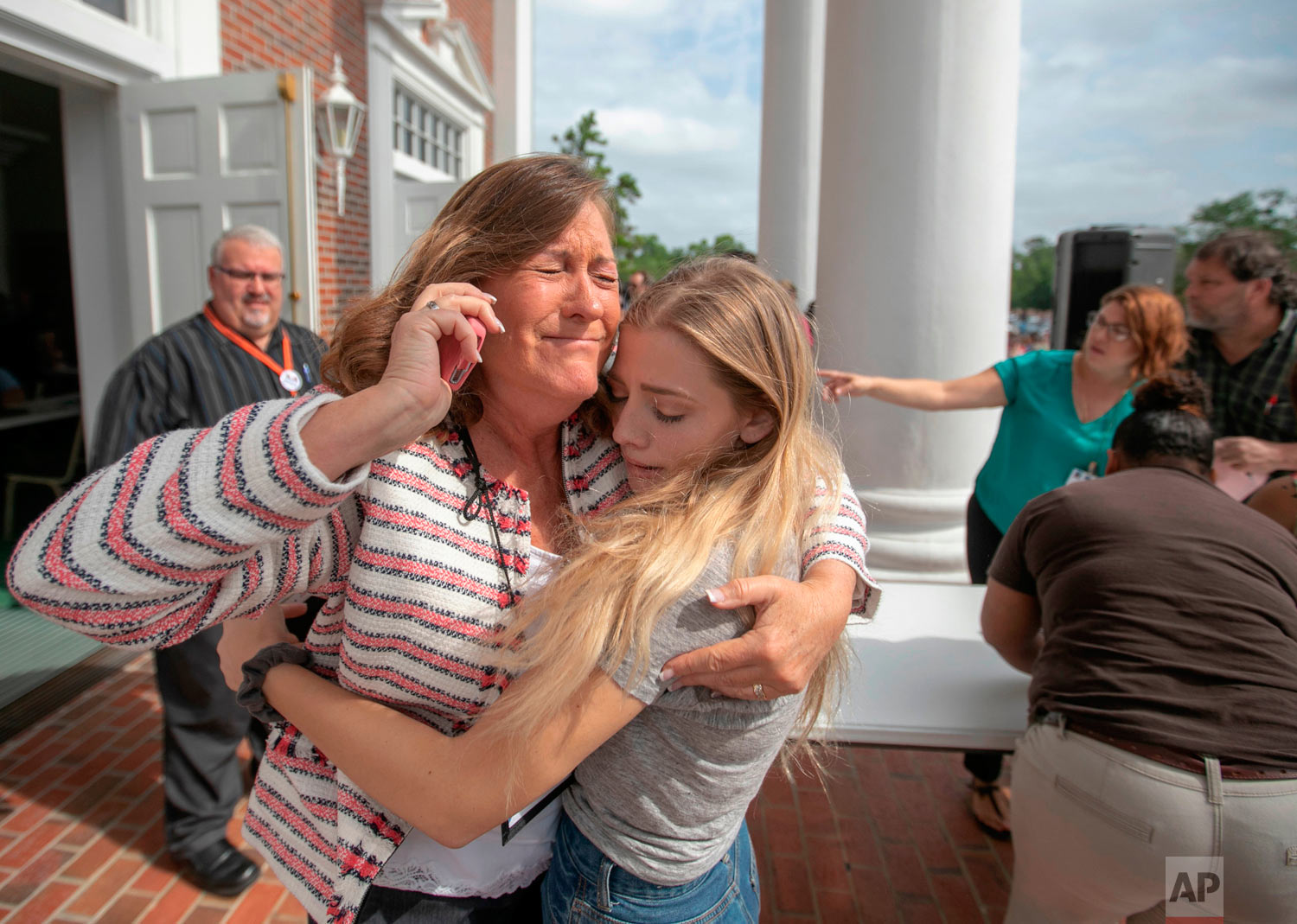 Judge Sarah Ritterhoff Williams embraces family friend student Attie French after finding her in the crowd at First Baptist Church while looking for her own daughter following a shooting at Forest High School, Friday 20, 2018 in Ocala, Fla. One student shot another in the ankle at the high school and a suspect is in custody, authorities said Friday. The injured student was taken to a local hospital for treatment. (Alan Youngblood/Star-Banner via AP)