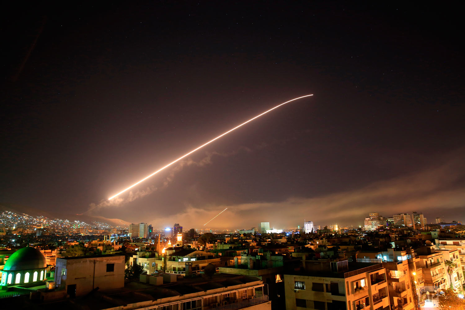 The Damascus sky lights up missile fire as the U.S. launches an attack on Syria targeting different parts of the capital early Saturday, April 14, 2018. Syria's capital has been rocked by loud explosions that lit up the sky with heavy smoke as U.S. President Donald Trump announced airstrikes in retaliation for the country's alleged use of chemical weapons. (AP Photo/Hassan Ammar)