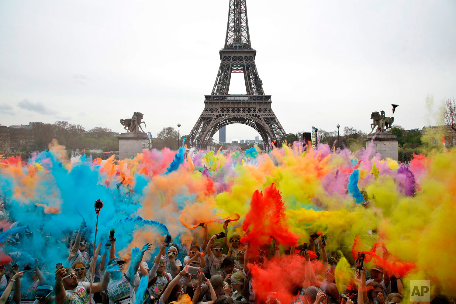 People throw colored powder as they celebrate at the end of the Color Run 2018 race in front of the Eiffel Tower in Paris, Sunday, April 15, 2018. The Color Run is a 5 kilometer (3.1 mile) running event where participants are covered in bright colored powder at each check station and is less about speed and more about enjoying a day with friends and family. (AP Photo/Thibault Camus)