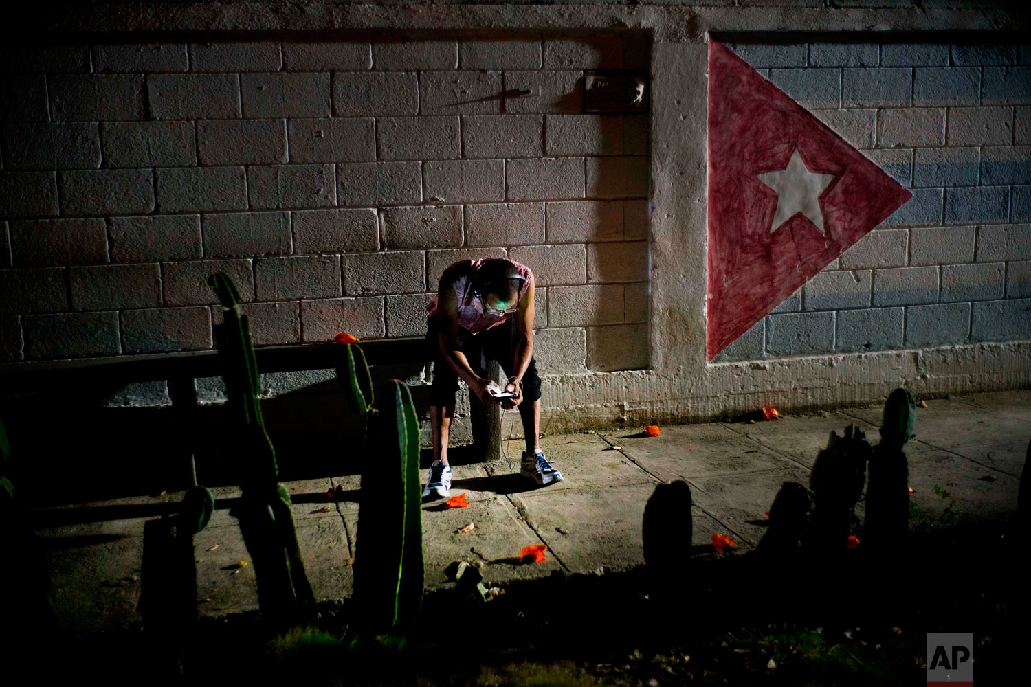 "Lazaro Rodriguez, 42, connects his cellphone at a public internet hot spot at night in Havana, Cuba on Saturday, April 14, 2018. Lazaro, who studied baking and is currently working in maintenance, said he's seen very positive changes in the economy in recent years, and would like to see development continue. ""The generation that comes after me will have much more. I lived 'the special period' in the 90s, and the country is still blocked,"" referring to the U.S. embargo. (AP Photo/Ramon Espinosa)"