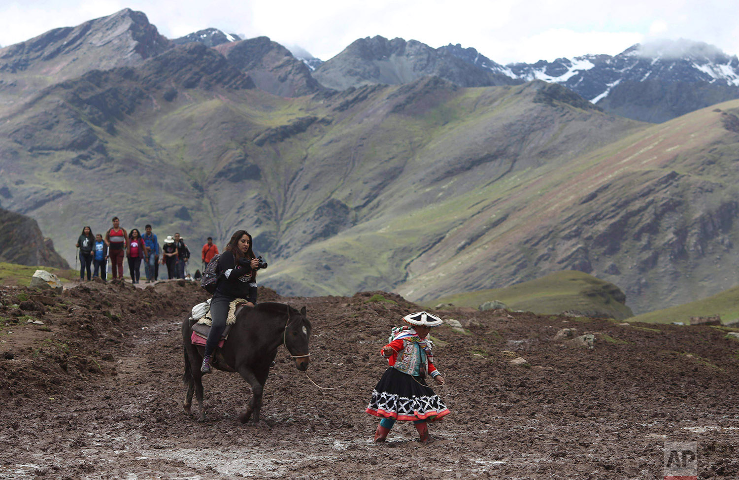 In this March 2, 2018 photo, a group of tourists ride horses led by an Andean guide to Rainbow Mountain, a ridge of multicolored sediments laid down millions of years ago and pushed up as tectonic plates clashed, in Pitumarca, Peru. (AP Photo/Martin Mejia)