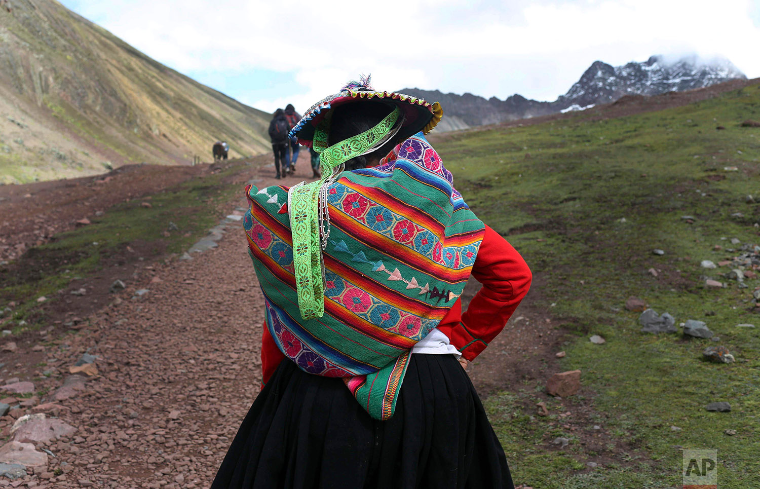 In this March 2, 2018 photo, an Andean woman walks to Rainbow Mountain in Pitumarca, Peru. (AP Photo/Martin Mejia)