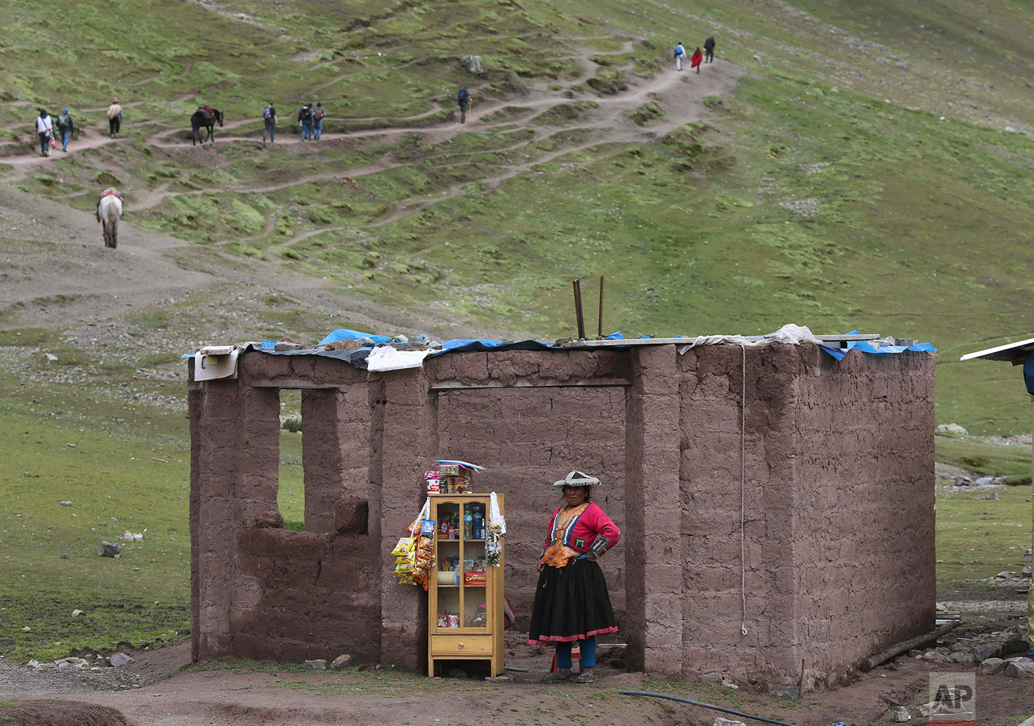 In this March 2, 2018 photo, an Andean woman sells candies, water and chips, on the route to Rainbow Mountain, in Pitumarca, Peru. (AP Photo/Martin Mejia)