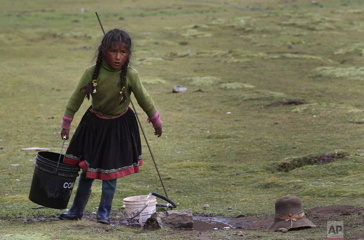 In this March 2, 2018 photo, a child hauls a bucket of water in Pitumarca, Peru, near Rain Mountain. (AP Photo/Martin Mejia)