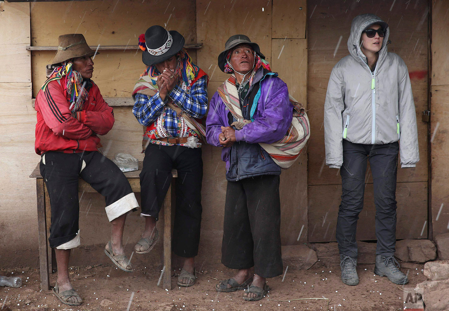 In this April 5, 2018 photo, Andean muleteers and a tourist take cover from a rain shower during a tour to Rainbow Mountain, in Pitumarca, Peru. (AP Photo/Martin Mejia)
