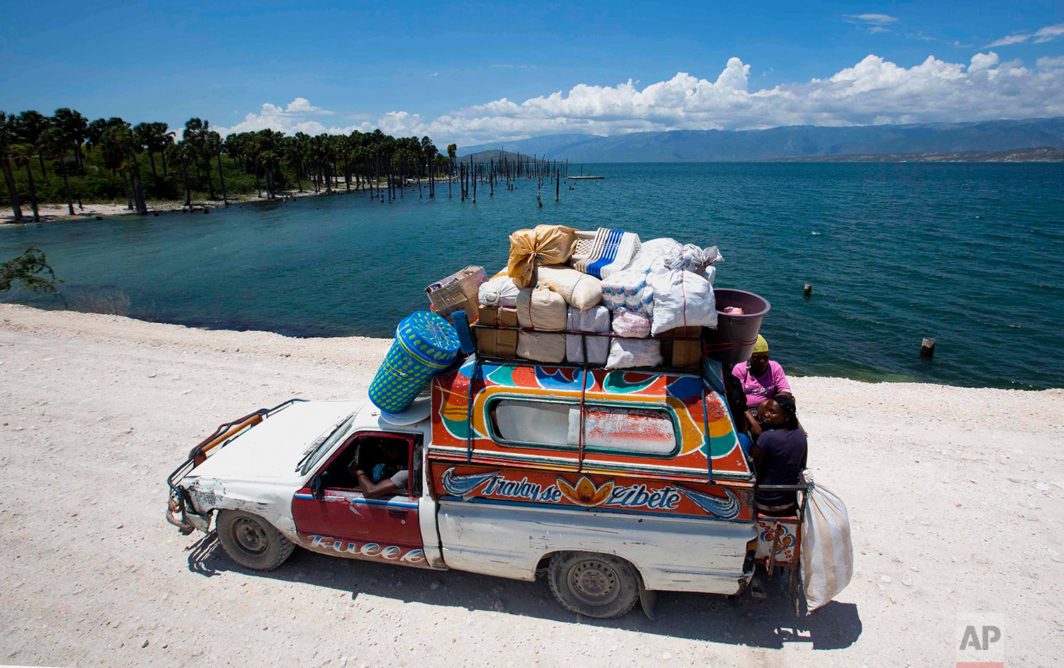 In this April 26, 2018 photo, people ride in a loaded truck, serving as public transportation, on the highway that leads to the Dominican Republic along the shore of Lake Azuei in Fond Parisien, Haiti.(AP Photo/Dieu Nalio Chery)