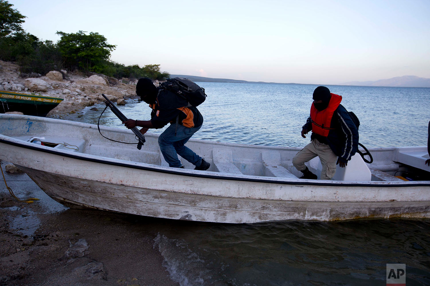 In this April 17, 2018 photo, two Taino Aqua Fish farm security guards return to shore at dawn after sleeping on the lake in two different locations to keep watch over fish cages on Lake Azuei in Fond Parisien, Haiti. The company has 60 employees, including security guards who keep watch during the night to keep thieves from raiding the cages. (AP Photo/Dieu Nalio Chery)