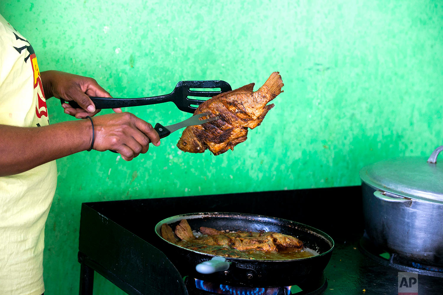 In this April 26, 2018 photo, Marjorie Dorcena cooks tilapia from Taino Aqua Fish farm for a guest staying at a small hotel known as a guest house in Fond Parisien, Haiti. In a country where most people live on less than $2 a day, Taino tilapia costs about $3.50 a pound, which is $2 less than the more common pink fish. (AP Photo/Dieu Nalio Chery)