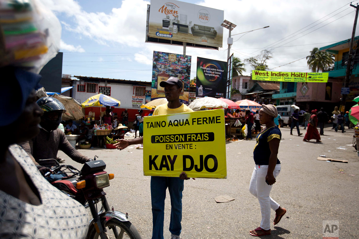 In this April 27, 2018 photo, Taino Aqua Fish worker Bernard Pierre Emil advertises that their tilapia fish can be bought at a stall outside the Kay Djo supermarket in Petion-Ville, Haiti. Taino markets its crop, which can reach 20,000 pounds a week, to small, informal markets as well as supermarkets, hotels and restaurants. (AP Photo/Dieu Nalio Chery)