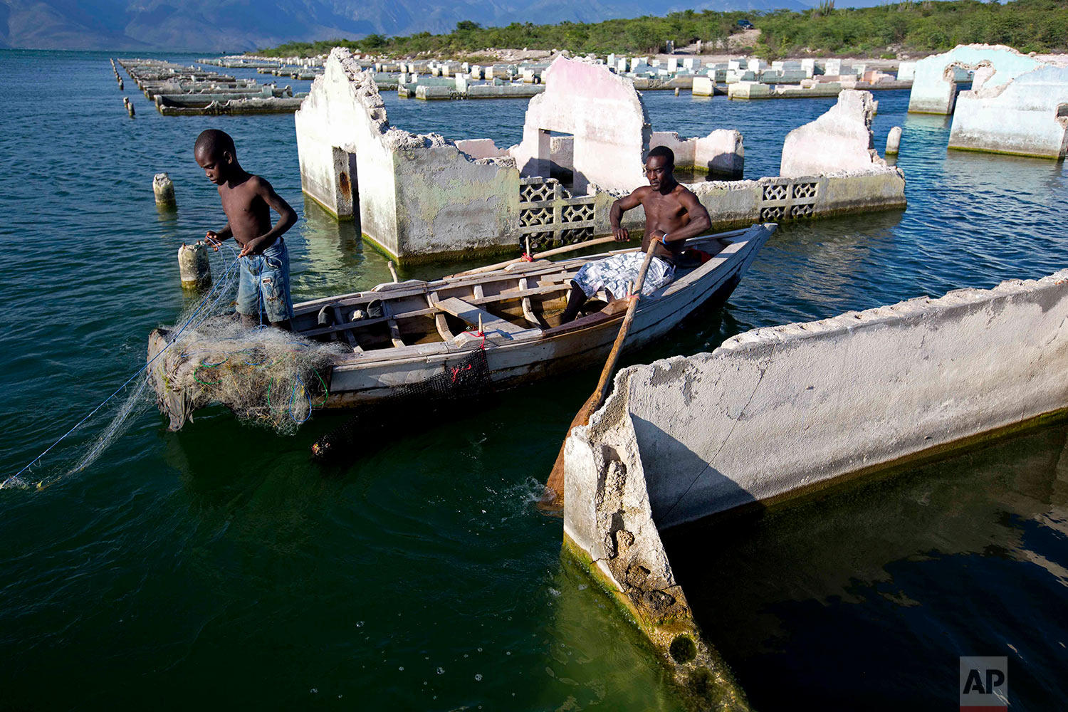 """In this April 20, 2018 photo, fisherman Miguel Louis checks on his nets with his 12-year-old son Dabens Louis, placed amid old, abandoned flooded homes on Lake Azuei in Fond Parisien, Haiti. A fish farming company growing tilapia set up their operation on this lake in 2014. """"Even small fish are hard to find"""" said Louis. (AP Photo/Dieu Nalio Chery)"""