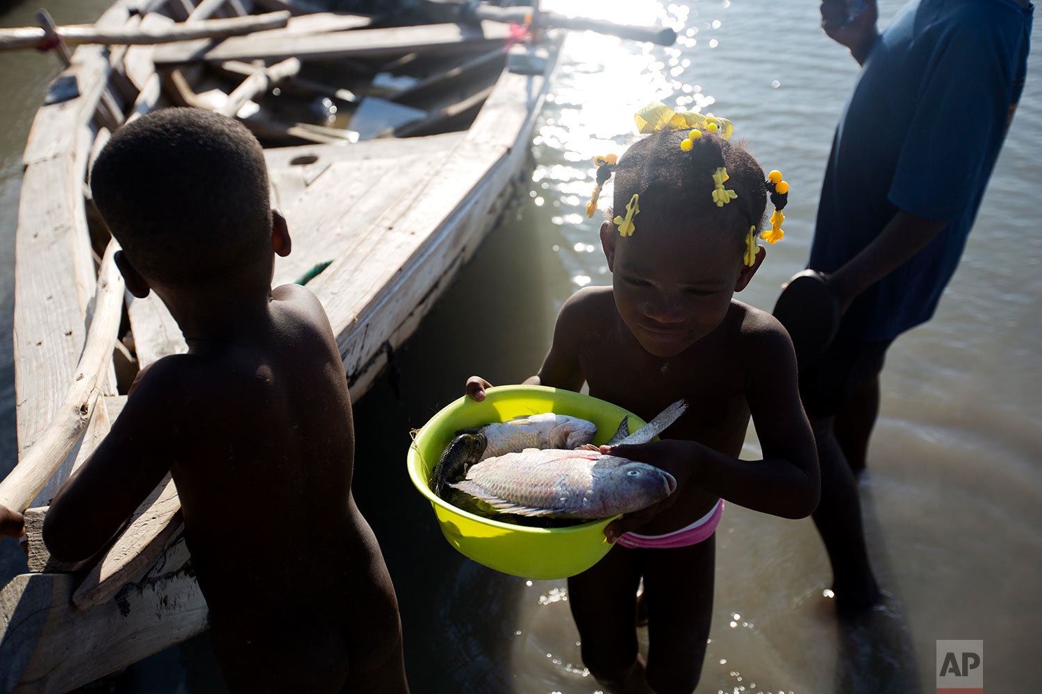 In this April 26, 2018 photo, Gerline Louis, the six-year-old daughter of fisherman Miguel Louis, carries the five fish her father caught in Lake Azuei in Fond Parisien, Haiti. Most people in this small border town, like Louis' family, get most of their meals from fish from the lake. (AP Photo/Dieu Nalio Chery)