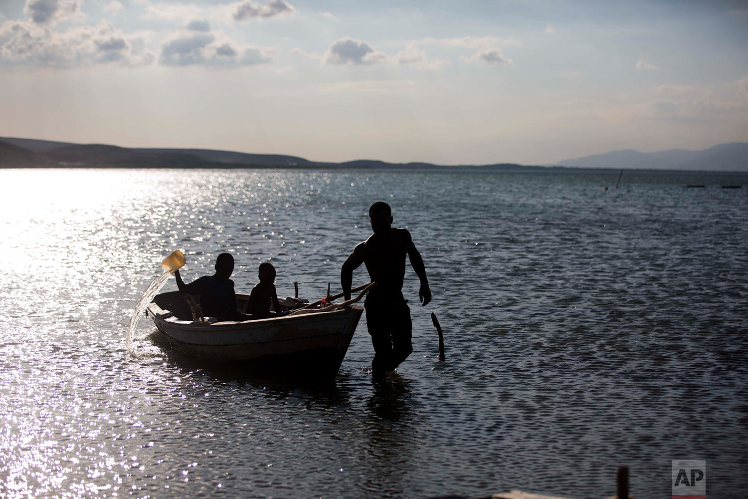 In this April 26, 2018 photo, fisherman Miguel Louis pulls his children in his boat after checking on his nets set up in Lake Azuei in Fond Parisien, Haiti. His 12-year-old son Dabens Louis bales water from the old, wooden boat, due to a small hole. (AP Photo/Dieu Nalio Chery)