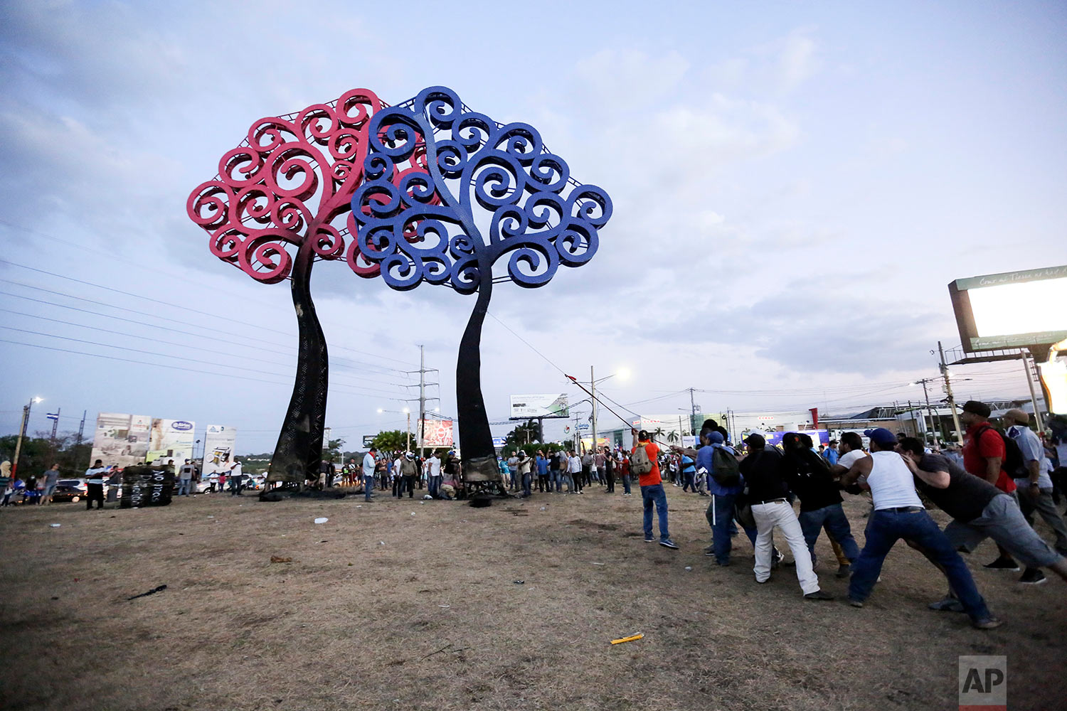 Anti-government protesters pull down a statue that is emblematic of the government of Nicaraguan President Daniel Ortega, at the Jean Paul Jennie round-about in Managua, Nicaragua, Saturday, April 21, 2018. Ortega said Saturday that his government is willing to enter into talks over social security reforms that have sparked four days of protests and clashes in which, rights monitors say, at least 25 people have died. A journalist covering the unrest was also killed. (AP Photo/Alfredo Zuniga)