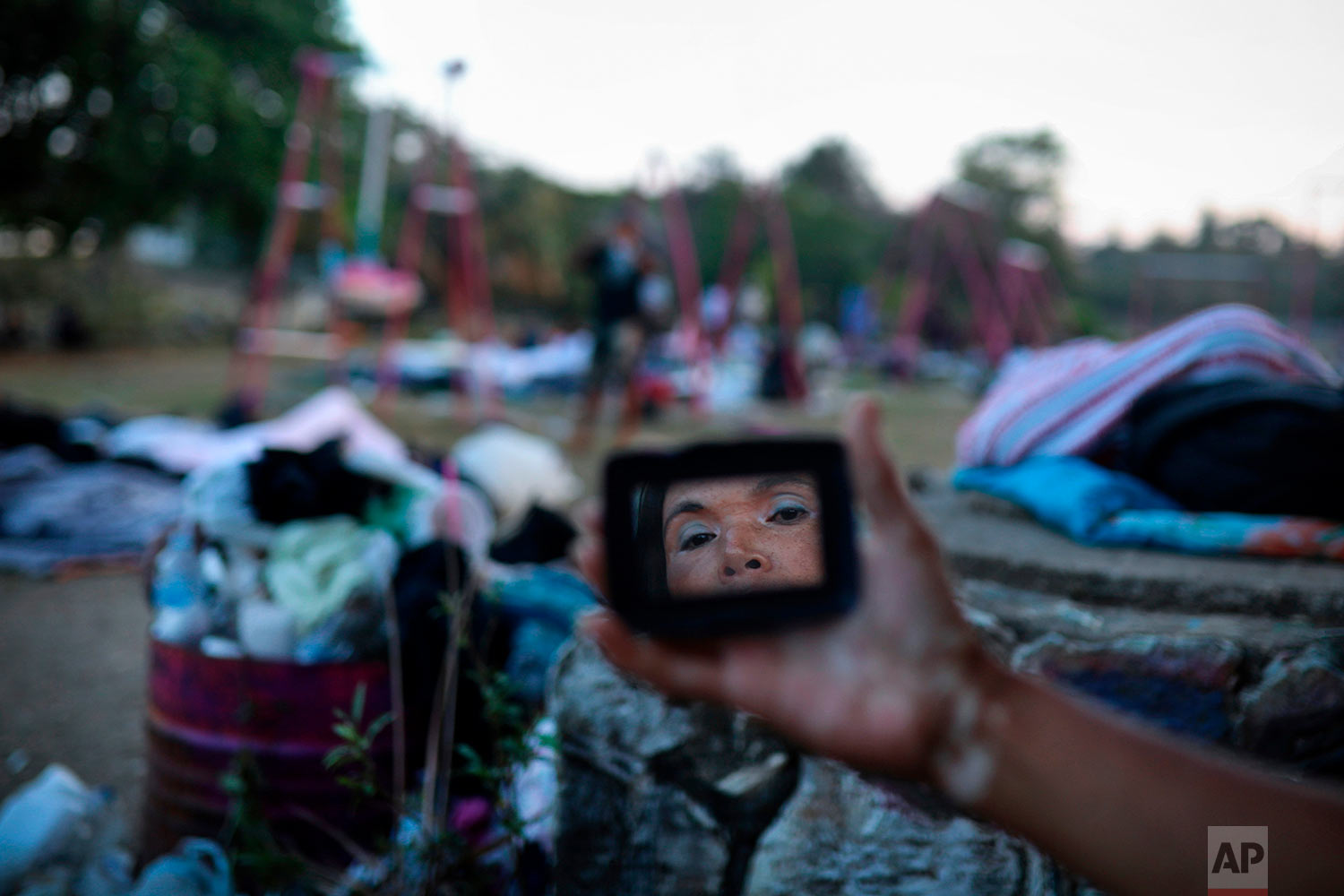 """A woman is reflected in a mirror as she gets ready for the day, as Central American migrants traveling with the annual """"Stations of the Cross"""" caravan wake up at a sports club in Matias Romero, Oaxaca State, Mexico, April 3, 2018. The caravan of Central American migrants that angered U.S. President Donald Trump was sidelined at a sports field in southern Mexico with no means of reaching the border even as Trump tweeted another threat to Mexico Tuesday. (AP Photo/Felix Marquez)"""
