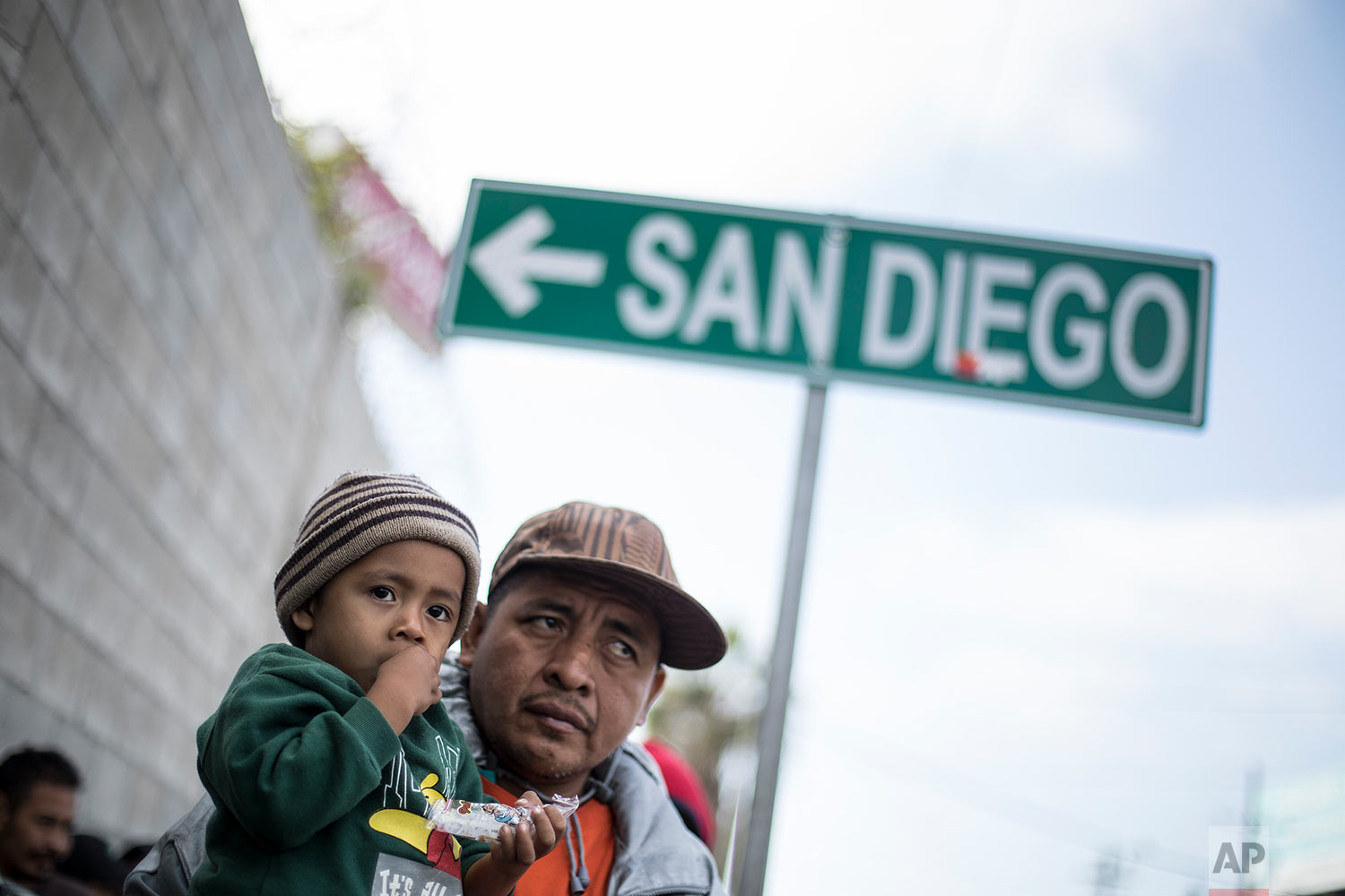 A father and his son await tutorship by immigration lawyers in Tijuana, Mexico, Friday, April 27, 2018. Close to to 200 migrants from Central America, mostly from Honduras, arrived in Tijuana seeking to enter the United States. (AP Photo/Hans-Maximo Musielik)