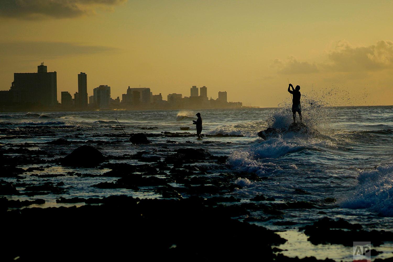 Fishermen prepare their fishing rods on Chivo beach as the sun sets in Havana, Cuba, Thursday, April 12, 2018. (AP Photo/Ramon Espinosa)