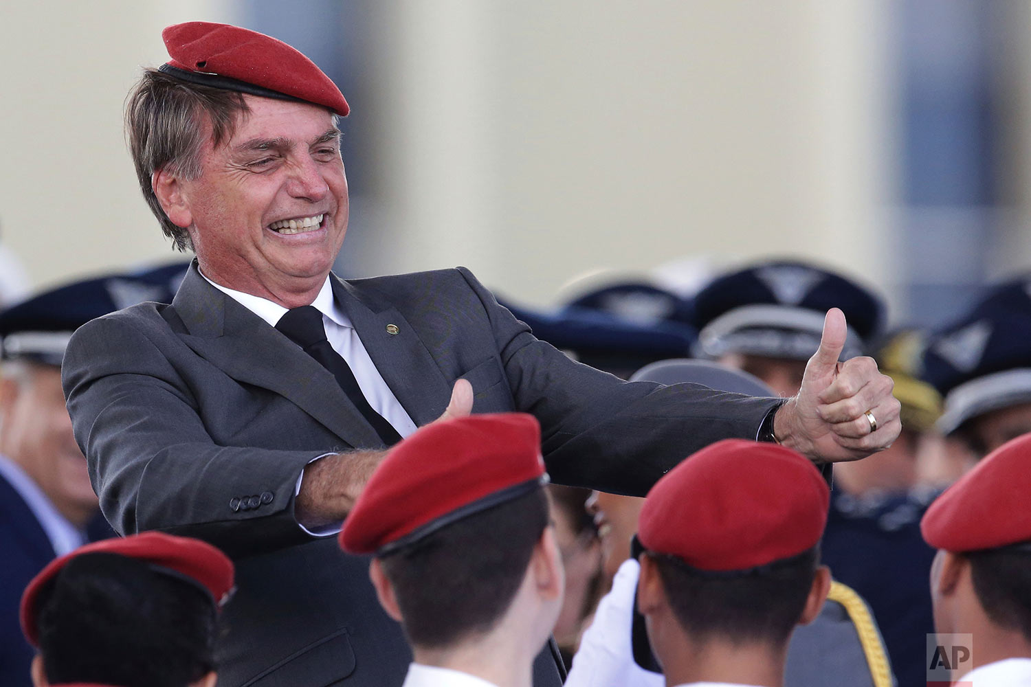 Presidential hopeful, conservative lawmaker Jair Bolsonaro flashes two thumbs up as he poses for a photo with cadets during a ceremony marking Army Day, in Brasilia, Brazil, Thursday, April 19, 2018. (AP Photo/Eraldo Peres)