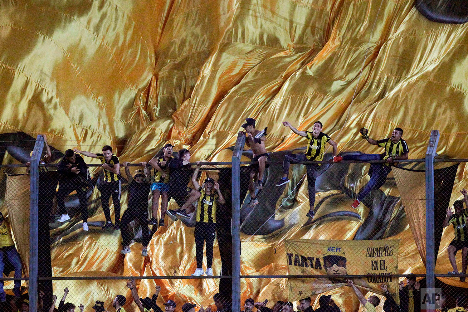 In this April 4, 2018 photo, Uruguay's Penarol fans cheer before the start of a Copa Libertadores soccer match against Argentina's Atletico Tucuman in Montevideo, Uruguay. (AP Photo/Matilde Campodonico)
