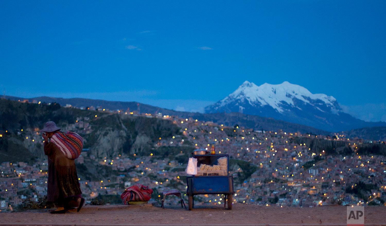 """A woman walks along Pereferica Avenue, past a street stall of popcorn, known as """"pipocas,"""" backdropped by the snow-capped Illimani Mountain, at sunset in La Paz, Bolivia, Tuesday, April 24, 2018. Illimani is part of the Cordillera Real in the Andes of South America. (AP Photo/Juan Karita)"""