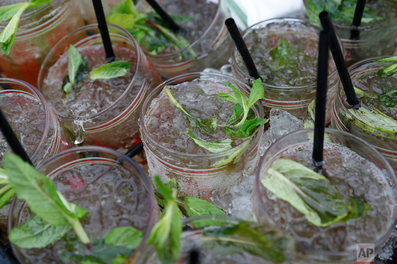 A vendor carries a tray Mint Julep glasses before the 144th running of the Kentucky Derby horse race at Churchill Downs Saturday, May 5, 2018, in Louisville, Ky. (AP Photo/Jeff Roberson)
