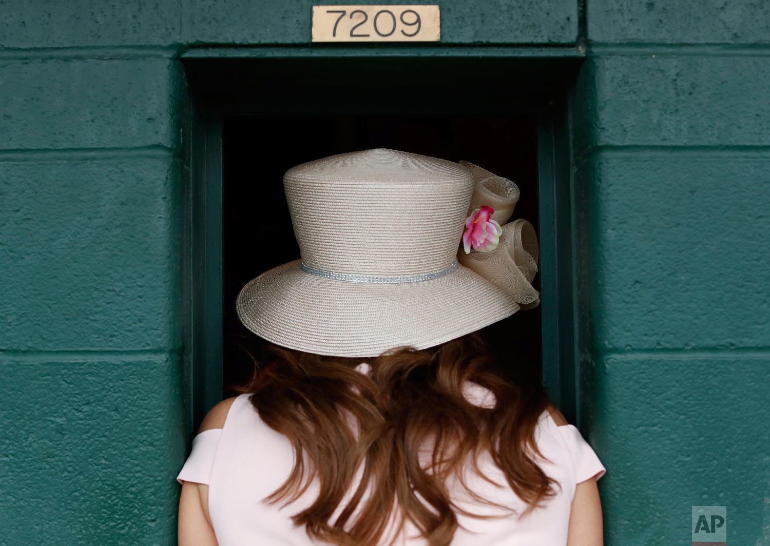 A women places a bet before the 144th running of the Kentucky Oaks horse race at Churchill Downs Friday, May 4, 2018, in Louisville, Ky. (AP Photo/John Minchillo)
