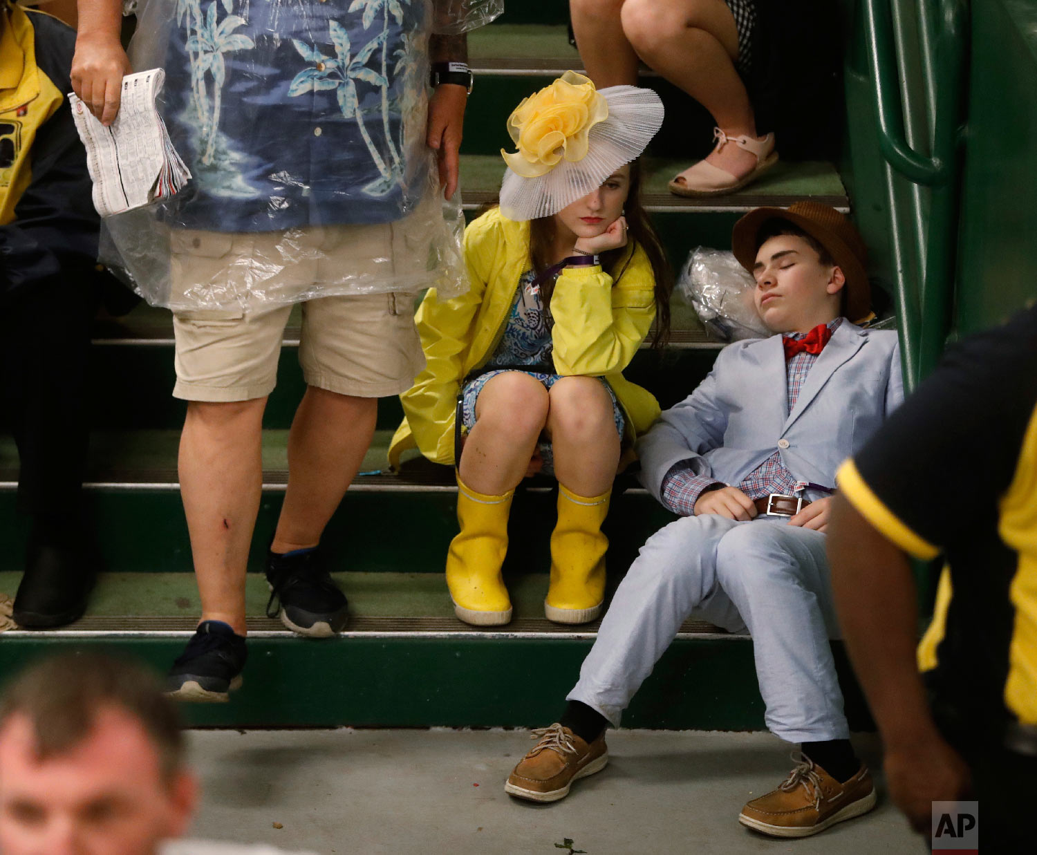 Fans take shelter from the rain before the 144th running of the Kentucky Derby horse race at Churchill Downs Saturday, May 5, 2018, in Louisville, Ky. (AP Photo/John Minchillo)