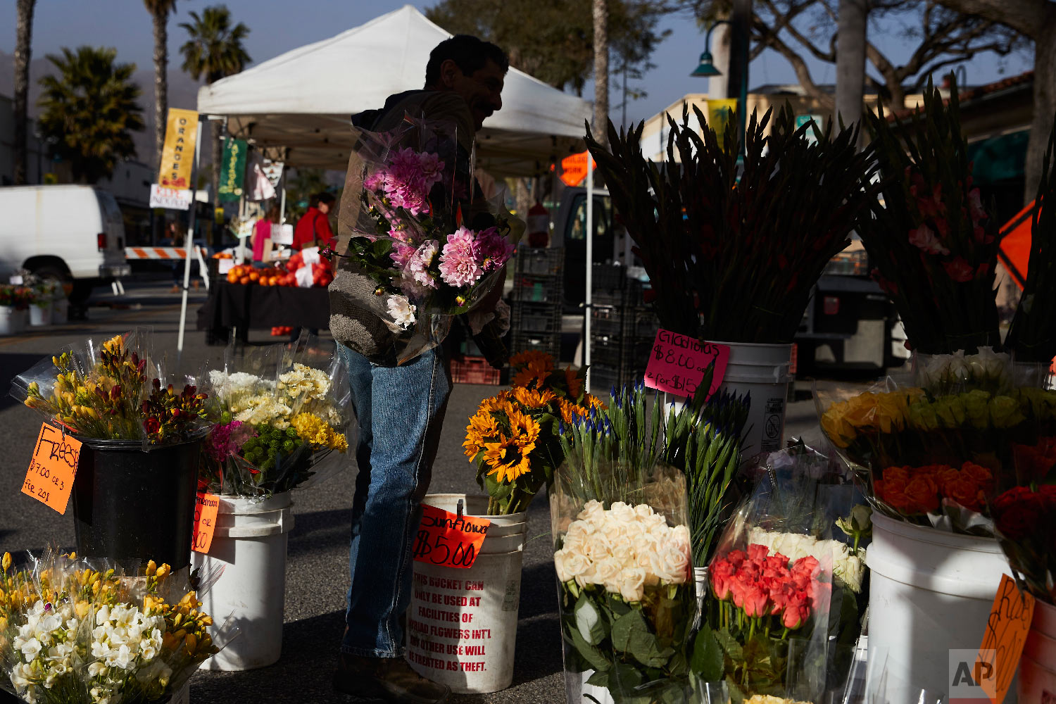 A man buys locally grown flowers at a farmers' market Thursday, April 12, 2018, in Carpinteria, Calif. (AP Photo/Jae C. Hong)