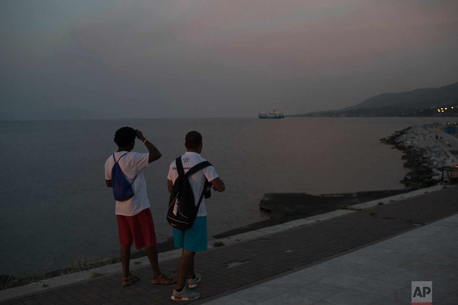 Two men watch the ferry leaving the port of Mytilene on the northeastern Aegean island of Lesbos, Greece on Thursday, May 4, 2018.  (AP Photo/Petros Giannakouris)