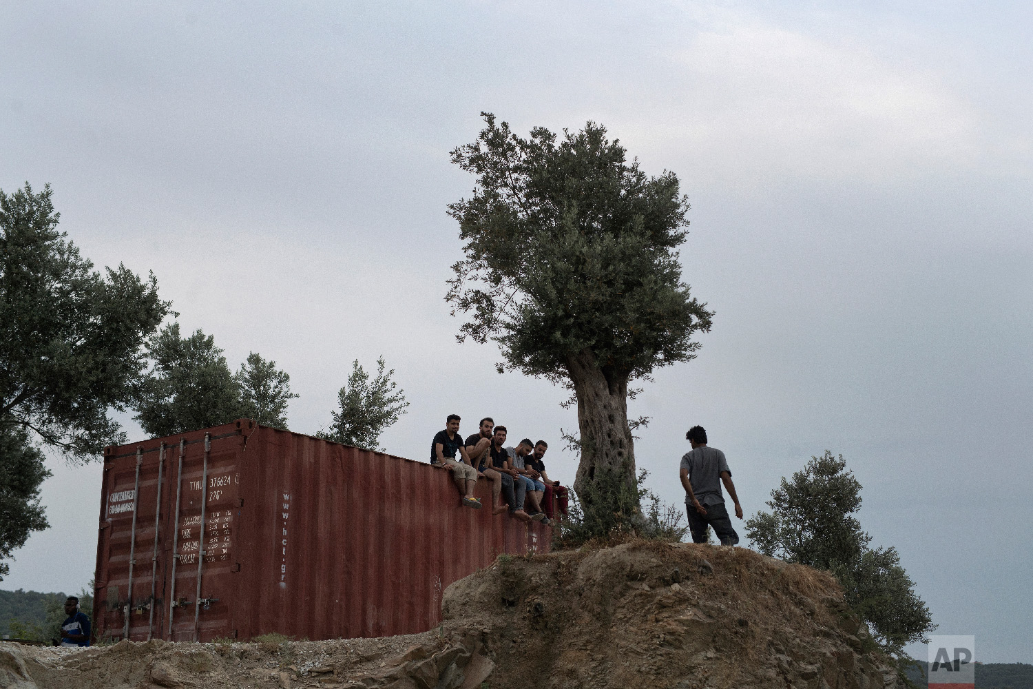 Refugees and migrants sit on the top of a container at a makeshift camp outside Moria on the northeastern Aegean island of Lesbos, Greece on Saturday May 5, 2018. (AP Photo/Petros Giannakouris)