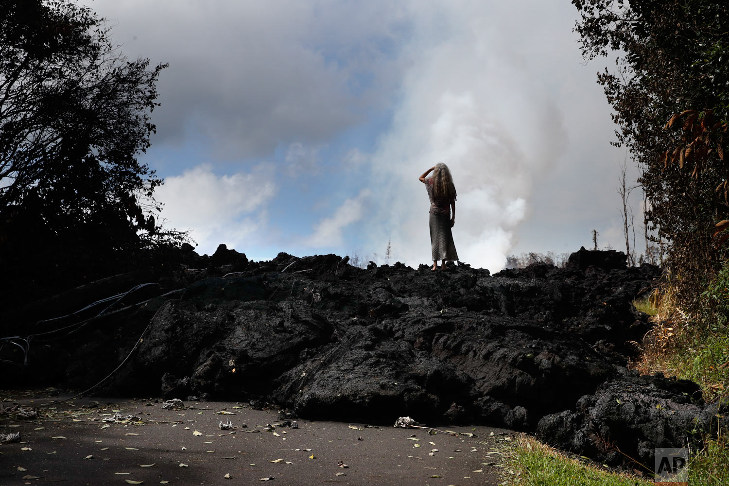Hannique Ruder, a 65-year-old resident living in the Leilani Estates subdivision, stands on a mound of hardened lava near Pahoa, Hawaii on Friday, May 11, 2018. The Kilauea volcano has destroyed more than 35 structures since it began releasing lava from vents about 25 miles (40 kilometers) east of the summit crater. (AP Photo/Jae C. Hong)