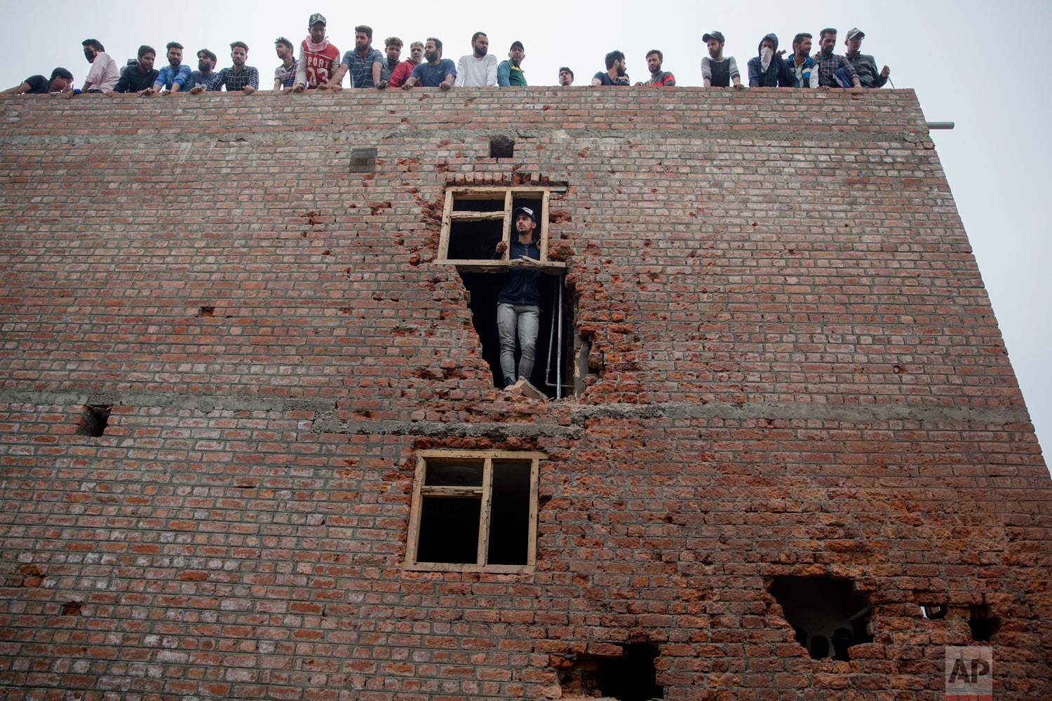 Kashmiri men inspect a house, damaged during a gun battle where suspected rebels were holed up, in Srinagar, Indian-controlled Kashmir, on Saturday, May 5, 2018. Fierce clashes erupted when residents in solidarity with the rebels tried to march to the gunbattle site. A vehicle belonging to Indian troops ran over and killed a man as protesters clashed with government forces, residents said. (AP Photo/Dar Yasin)
