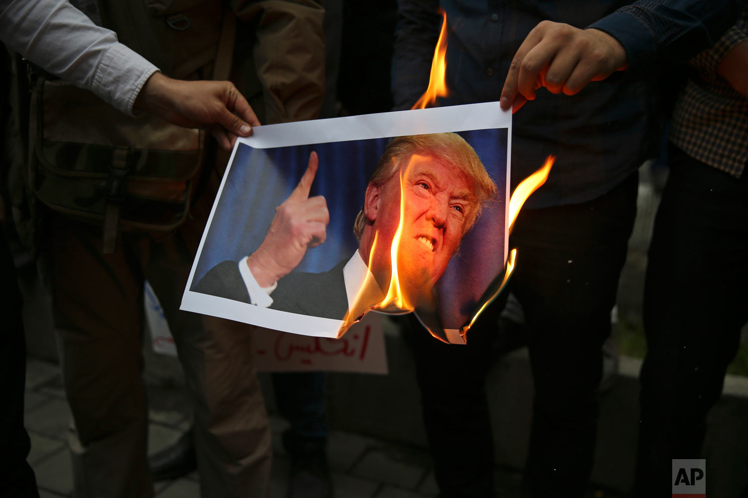 Demonstrators burn a picture of U.S. President Donald Trump during during a protest in front of the former U.S. embassy in Tehran, Iran, on Wednesday, May 9, 2018, in response to Trump's decision to pull out of the international nuclear deal and renew sanctions. (AP Photo/Vahid Salemi)