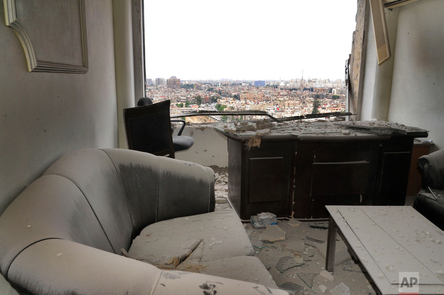 This photo released by the Syrian official news agency SANA shows damage inside a office that was hit by shelling, apparently by Islamic State fighters, in Damascus, Syria, Wednesday, May 9, 2018. Militants fired three mortar shells on the center of Damascus Wednesday killing several and wounding 14, Syria's state news agency said. (SANA via AP)
